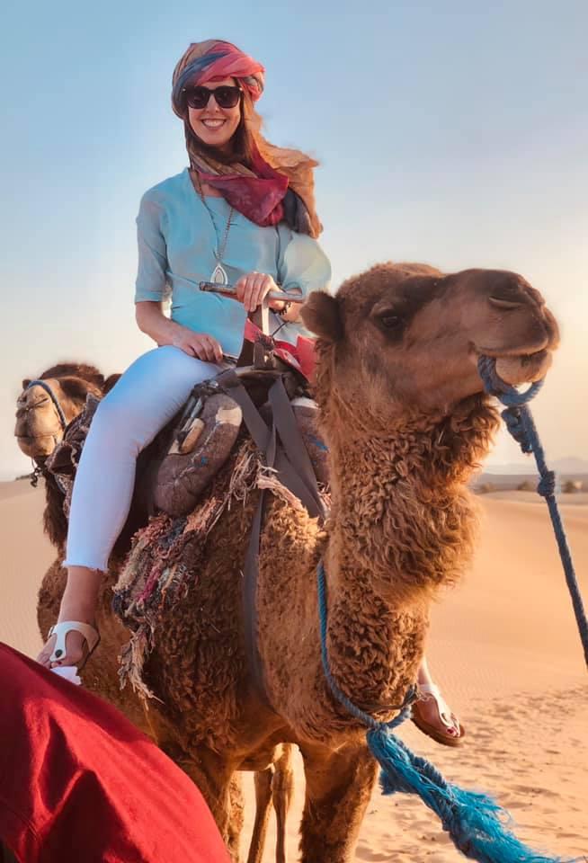 Luxury Travel Advisor, Magi Arnold riding a camel through the Sahara Desert on a Morocco vacation